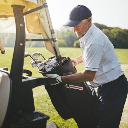 Senior golfer placing his golf club bag onto a cart