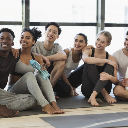 Happy multicultural friends taking selfie on smartphone after fitness training