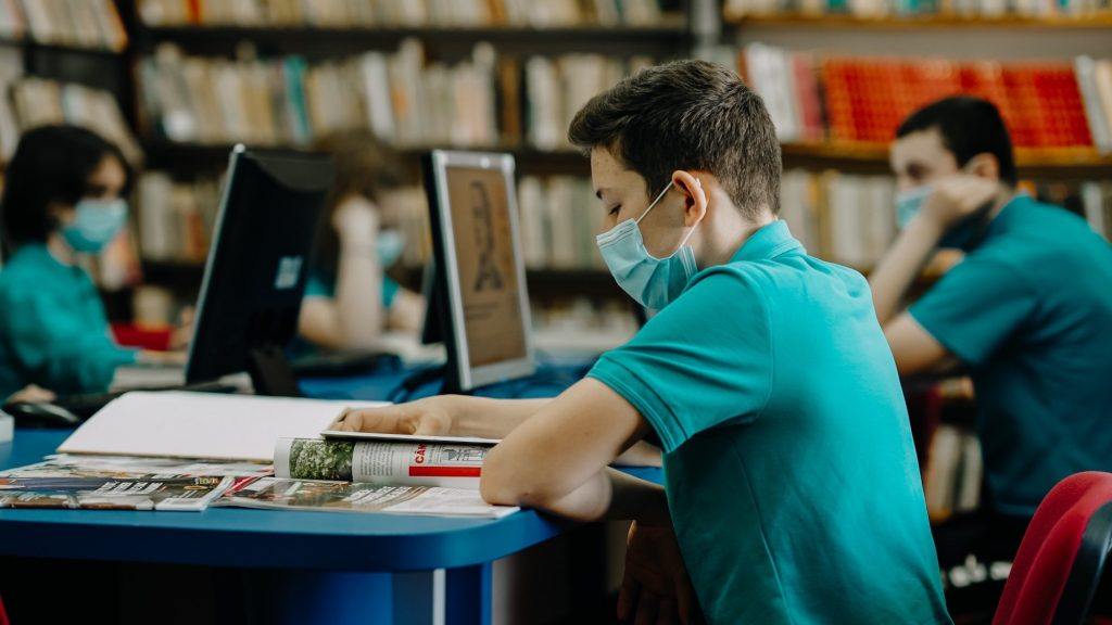 Encourage A Healthy Lifestyle. Student studying with a mask on.