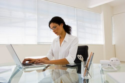 Middle aged lady working at a desk in a corporate office