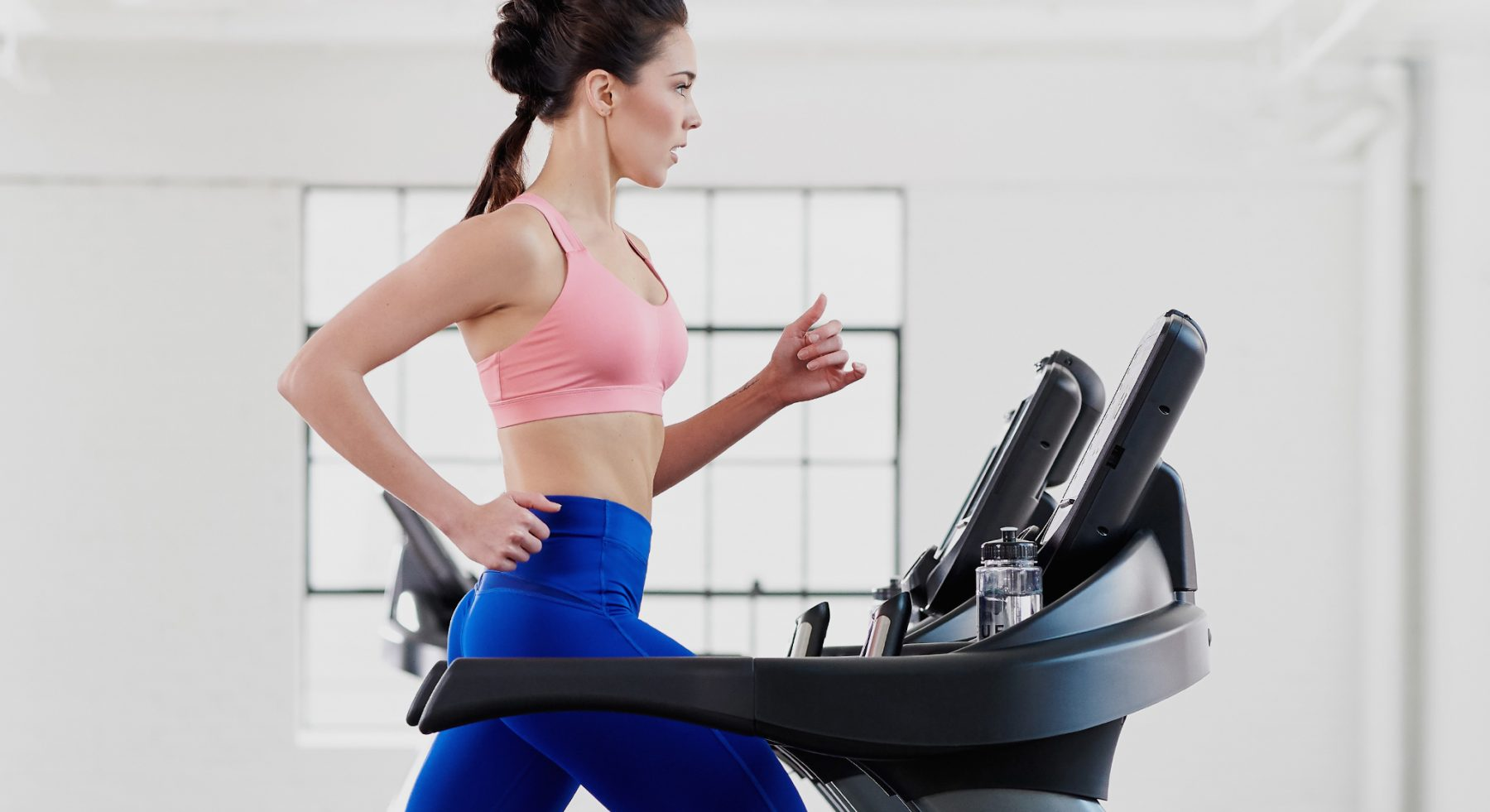 Woman running on TRUE's commercial fitness equipment. See all of our products.